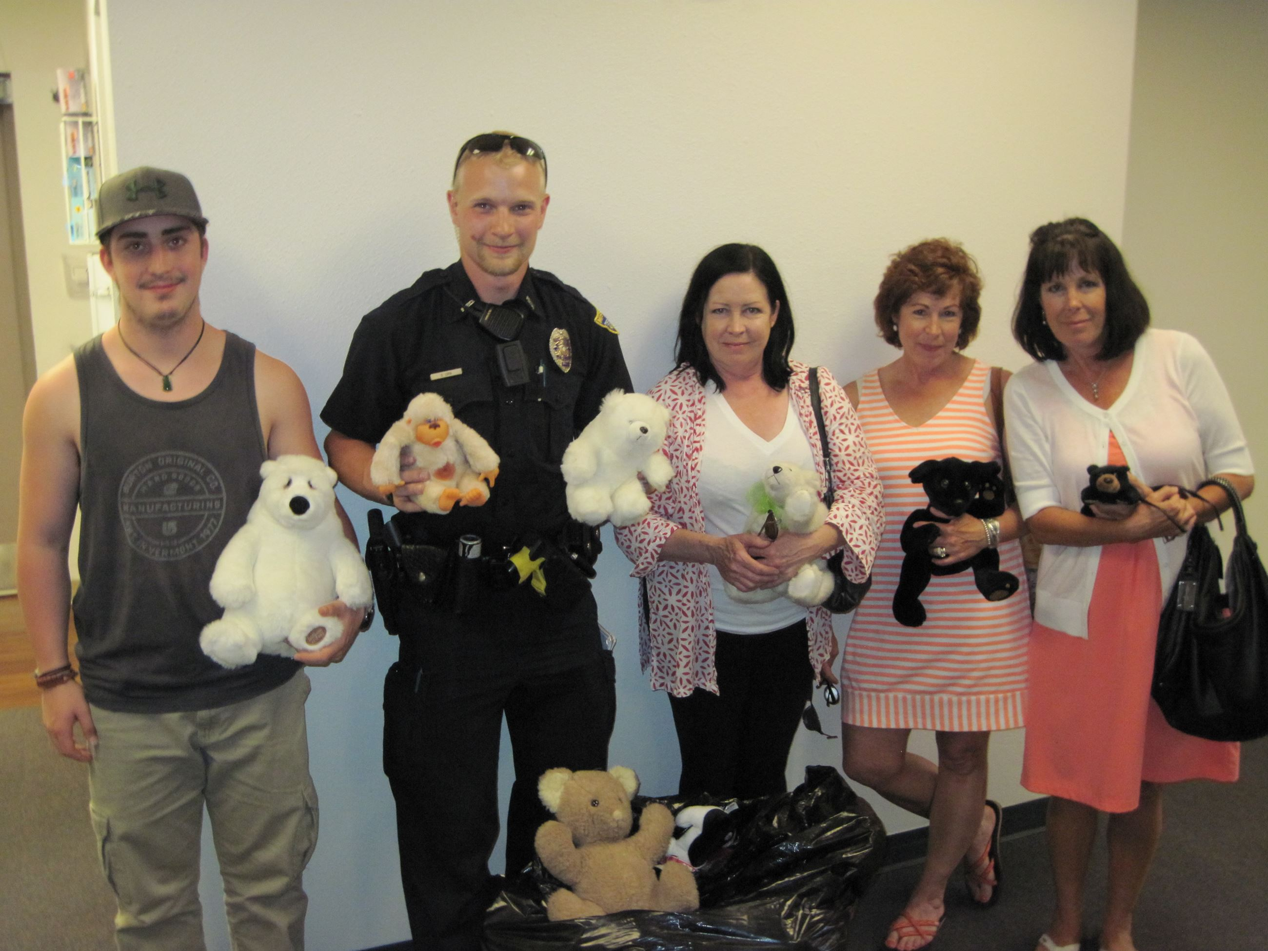 Group of People Holding Stuffed Animals Standing with a Police Officer