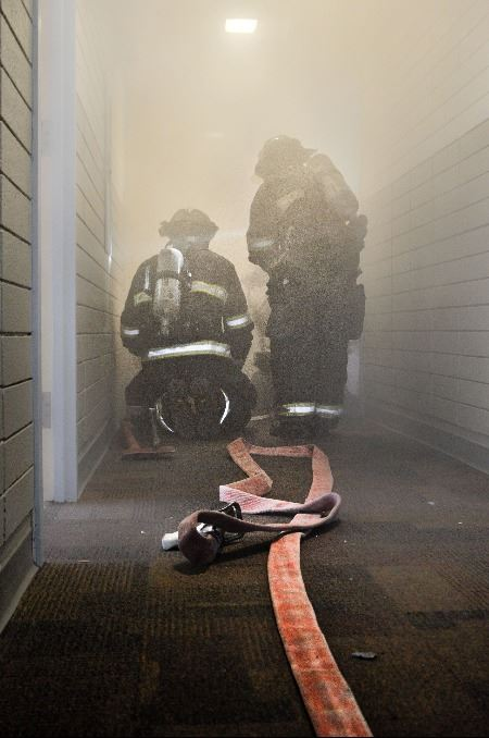 Firefighters with a water hose